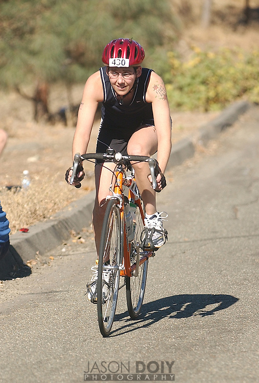 Deb Mosley during the final portion of the biking leg of her triathalon at Lake Berryessa. Mosley's time was 2 hours 3 minutes for the half-mile swim, 15-mile bike and 4-mile run...Photo by Jason Doiy.10-9-04.027-2004.
