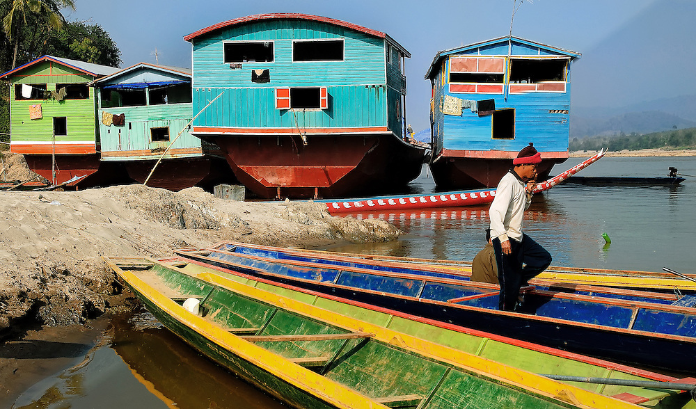 Small passenger and large cargo boats moored on the Mekong river at Pak Lai, Laos.