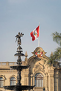 Flag of Peru on Palacio Gobierno (Government Palace) and bronze water fountain in Plaza Mayor; Lima, Peru.