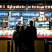 Customers line up for coffee and other fast foods at a small food counter next to the Eiffel Tower in Paris.