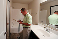 Kevin Hunter of Hunter Appraisal Service makes notes in one of the bathrooms as he reviews a new construction home at 403 Cimarron Drive, in Hiawatha on Friday morning, June 29, 2012.