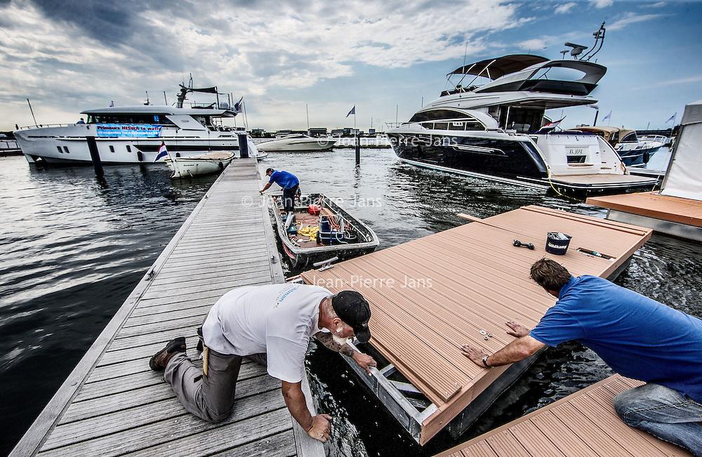 Nederland, Amsterdam, 26 augustus 2016.<br /> Hiswa te water.<br /> De HISWA te water vindt van 30 augustus tot en met 4 september plaats in de Amsterdam Marina op de NDSM-werf. De grootste in- water bootshow van Noord-Europa toont 300 boten, honderden watersportartikelen en heeft een activiteitenprogramma voor jong en oud. Aan de HISWA te water nemen dit jaar circa 60 boten en productprimeurs deel. De beurs telt de meeste primeurs sinds 2012.<br /> Op de foto: Steigerbouwers leggen de hand aan het aanleggen vd laatste steigers met op de achtergrond primeurboten zoals rechts de boot El Jefe genaamd.<br /> <br /> Netherlands, Amsterdam, August 26, 2016. <br /> HISWA in-water.The HISWA in-water takes place from 30 August to 4 September in Amsterdam Marina at the NDSM-shipyard. The largest in-water boat show in Northern Europe shows 300 boats, hundreds of water sports and has a program of activities for young and old. <br /> <br /> Want to buy a boat? Want to orientate on the latest models? Discover the latest trends in (inter)national yachts? Get tips from professionals? Meet the watersports? Visit the most complete in-water boatshow in Northern Europe at the NDSM shipyard. There are 300 brand new boats of 5-25 meters on the jetties and on the quay a wide range of nautical products. And on the water many exciting activities. Source: hiswatewater.nl<br /> <br /> <br /> Foto: Jean-Pierre Jans