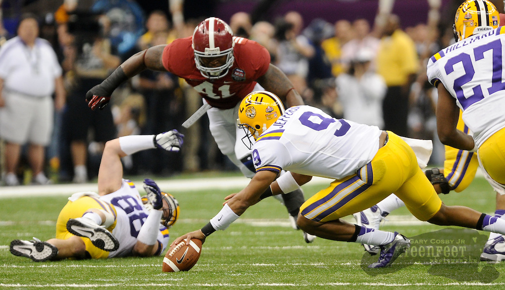 Daily Photo by Gary Cosby Jr.    ..Jordan Jefferson tries to recover his own fumble as Courtney Upshaw pursues the play during the first half of the BCS National Championship Game between Alabama and LSU in the Superdome Monday night...................................