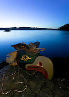 A First Nations mask, typical of the Native culture and craft on Northern Vacouver Island sits atop rocks at lowtide along a shoreline near Port Rupert.  Port Hardy, Northern Vancouver Island, British Columbia, Canada.