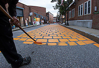 Larry Frates paints Canal Street orange on Wednesday evening transforming it into PumpCanaly for Saturday's Pumpkin Fest.  (Karen Bobotas/for the Laconia Daily Sun)