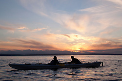 North America, United States, Washington, couple at rest in double kayak at sunset, with Olympic Mountains in distance.