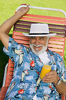 Senior Man in Lawn Chair Holding Orange Juice