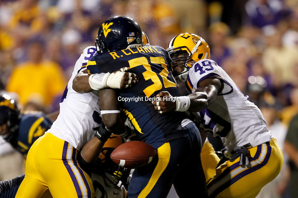Sep 25, 2010; Baton Rouge, LA, USA; LSU Tigers defensive end Sam Montgomery (99) and defensive end Barkevious Mingo (49) force a fumble as they wrap up West Virginia Mountaineers running back Ryan Clarke (32) during the first half at Tiger Stadium.  Mandatory Credit: Derick E. Hingle