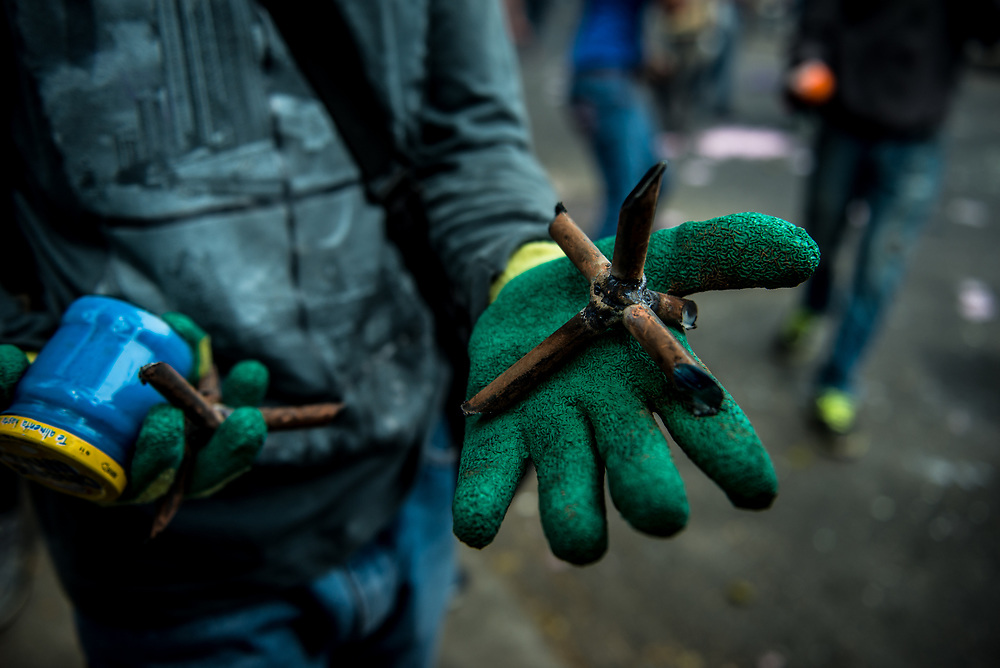 CARACAS, VENEZUELA - MAY 8, 2017:  Atn anti-government protester shows a journalist he homemade weapons he made to use in clashes against security forces. The streets of Caracas and other cities across Venezuela have been filled with tens of thousands of demonstrators for nearly 100 days of massive protests, held since April 1st. Protesters are enraged at the government for becoming an increasingly repressive, authoritarian regime that has delayed elections, used armed government loyalist to threaten dissidents, called for the Constitution to be re-written to favor them, jailed and tortured protesters and members of the political opposition, and whose corruption and failed economic policy has caused the current economic crisis that has led to widespread food and medicine shortages across the country.  Independent local media report nearly 100 people have been killed during protests and protest-related riots and looting.  The government currently only officially reports 75 deaths.  Over 2,000 people have been injured, and over 3,000 protesters have been detained by authorities.  PHOTO: Meridith Kohut