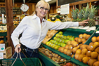 Portrait of a senior woman shopping for pineapples in produce market