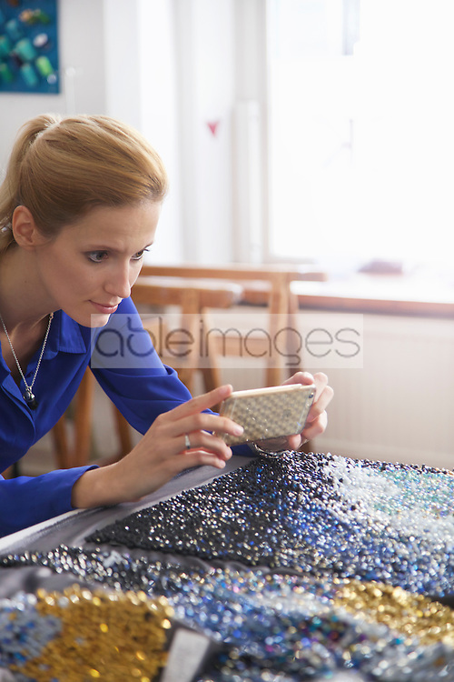 Woman Taking Photo of Beaded Fabric at Embroidery Design Studio