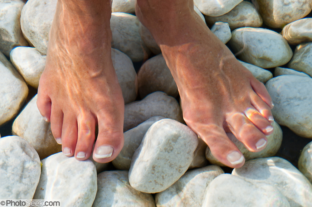 Feet are massaged by stones in a cold public bath in Kastelruth/Castelrotto,  a comune in Südtirol/South Tyrol/Alto Adige, in the Dolomites, Italy, near Bolzano and Seiser Alm (Alpe di Siusi). After Austria lost World War I, its South Tirol (Südtirol) became Italy's Alto Adige. German is the most spoken language in Kastelruth.