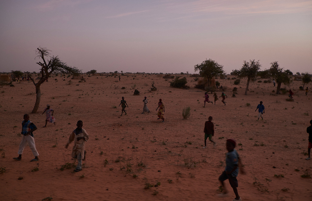 Children run along the side of a road at a makeshift camp of internally displaced people  by the side of the road on the highway outside of Diffa, Niger on February 11, 2016.Caritas undertook a distribution of two blankets per family in January, 2016. Most of the displaced families are from the village of Chilori, Niger close to the border with Nigeria and fled when Boko Haram attacked killing 10 people.
