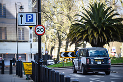 © Licensed to London News Pictures. 02/03/2020. LONDON, UK.  A taxi on Millbank passes by a 20 mile per hour sign.  A speed limit of 20mph has been imposed on all central London roads managed by Transport for London (TfL), under a scheme called Vision Zero, in a bid to reduce road deaths.  Effective 2 March, TfL roads within the congestion charge zone will be affected.  Photo credit: Stephen Chung/LNP