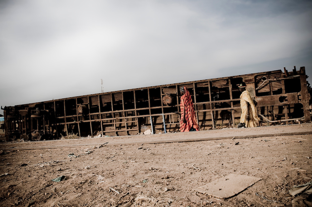 Two women walk past an overturned train car in the Southern Sudanese town of Aweil. Sudan recently voted on whether or not to remain with the North or to set out alone as the world's newest nation. (© William B. Plowman)