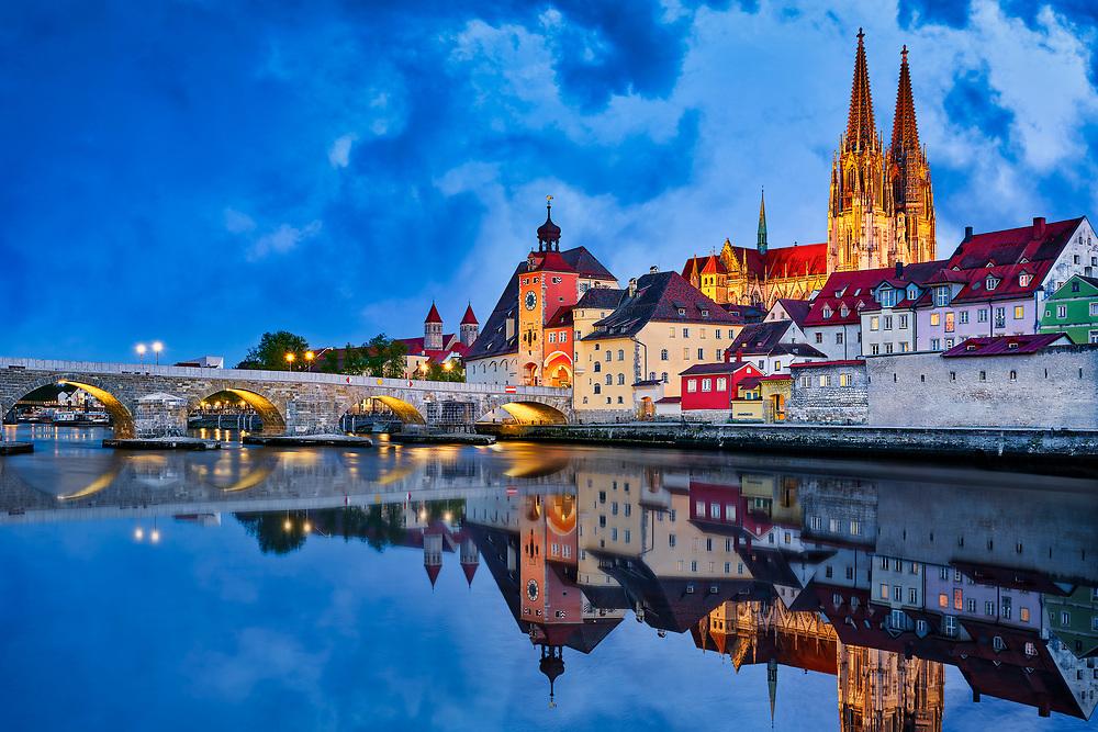Regensburg mit Stadtportal, Dom und Steinerne Brücke bei Nacht.