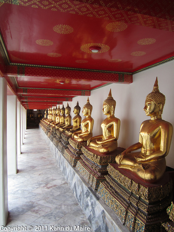 Row of Buddha statues at Wat Pho temple in Bangkok, Thailand. Golden!