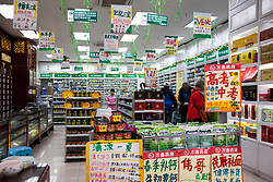 Bargain day at the local drug store.  A wall of tiny drawers on the left store medicines mysterious to westerners in this Chongqing pharmacy, central China. Elsewhere giant signs detail current specials on common everyday drug store items.