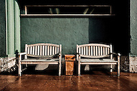 Two outdoor wooden benches separated by ashtray under hard wood floor in Oakland, CA.  Copyright 2009 Reid McNally.