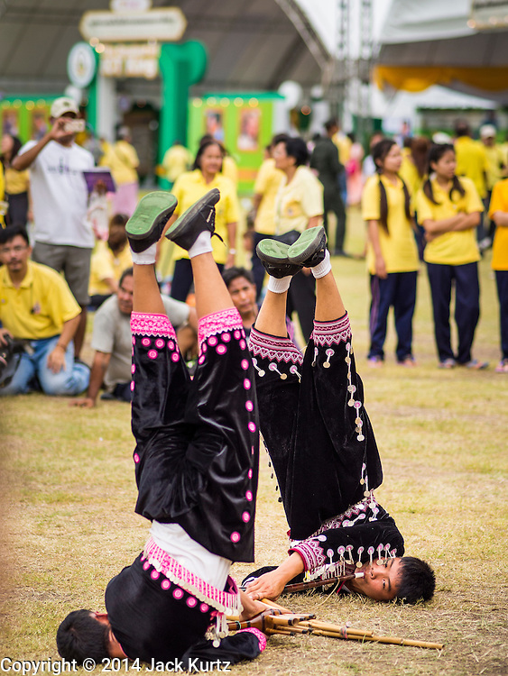 02 DECEMBER 2014 - BANGKOK, THAILAND: Hmong, members of an ethnic minority from northern Thailand, perform a traditional dance on Sanam Luang in Bangkok before the Trooping of the Colors, during a celebration of the King's Birthday. The Thai Royal Guards parade, also known as Trooping of the Colors, occurs every December 2 in celebration of the birthday of Bhumibol Adulyadej, the King of Thailand. The Royal Guards of the Royal Thai Armed Forces perform a military parade and pledge loyalty to the monarch. Historically, the venue has been the Royal Plaza in front of the Dusit Palace and the Ananta Samakhom Throne Hall. This year it was held on Sanam Luang in front of the Grand Palace.    PHOTO BY JACK KURTZ