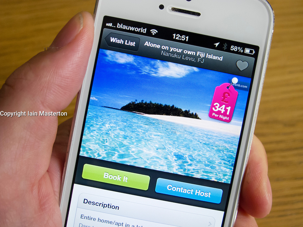 Using Airbnb app to book holiday accomodation on a private island with a white iPhone 5 smartphone