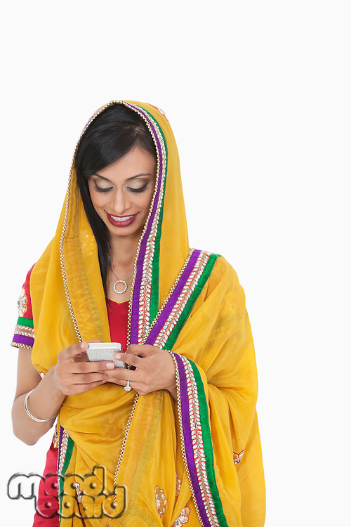 Indian female in traditional wear using cell phone over gray background