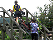 Jos en Hankie sjouwen de ligtandem een bruggetje over op de route.<br /> <br /> Two people are carrying their recumbent tandem over a bridge.
