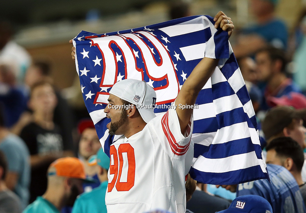 A New York Giants fan waves a flag while cheering for the team during the New York Giants NFL week 14 regular season football game against the Miami Dolphins on Monday, Dec. 14, 2015 in Miami Gardens, Fla. The Giants won the game 31-24. (©Paul Anthony Spinelli)