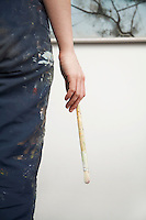 Woman holding paintbrush back view mid section