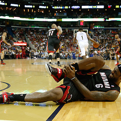 Mar 22, 2014; New Orleans, LA, USA; Miami Heat forward LeBron James (6) holds his ankle after falling under the goal during the third quarter of a game at the Smoothie King Center. The Pelicans defeated the Heat 105-95. Mandatory Credit: Derick E. Hingle-USA TODAY Sports
