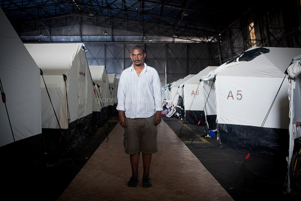 HAL FAR, MALTA - JUNE 21: Dawit (right), a 35 years immigrant old from Ethiopia, and Michael (center), a 25 years old immigrant from Eritrea, are here by the Swiss Red Cross tents inside the Hangar Open Center in Hal Far (which translates as &quot;Rat's Town&quot;) on June 21, 2011. <br /> <br /> Dawit was a language teacher in Tripoli and lived well, with no problems until the crisis started. He arrived in Malta on March 29th on a boat with 80 people after crossing the sea for 34 hours. &quot;Once the UN resolution against Libya was signed there were State TV announcements (also in English) that announced that migrants were free to leave the country. It wasn't possible before that date because of the agreement between Italy and Libya&quot;. No police or army forced them to leave, but there was some kind of general pressure to get sub-saharan migrants out of the country and to have them leave by boat. In Dawit's case, his landlord told him he had one day to leave his apartment. &quot;Buses in Tripoli were collecting people and deporting them&quot;, Dawit says. They couldn&rsquo;t go towards Tunisia or Egypt, only towards to the coast. Other sub-Saharans were able to flee to Tunisia, but there aren't any Ethiopian embassies in Libya, so Ethiopians in Libya don't have any documents that allowed them to stay in the country or officially cross borders. Once they arrived at the port they didn't pay any fixed fee but all they had was confiscated, including food and water. A boat was given to them and they left. &quot;People had bought food and water for their journey, but everything was confisfacted. I was lucky, because it took me only 34 hours to arrive in Malta, but it took these guys (indicating Michael, 25, and Mubarak, 23, both from Ethiopia, standing next to him - not in this picture) 10 days to arrive&quot;, Dawit says.Dawit continues: &quot;Life was good in Libya. We were all supporting our families. If wanted we could have left before, when everybody was leaving Libya (referring to 2008). But the price to reach Europe was