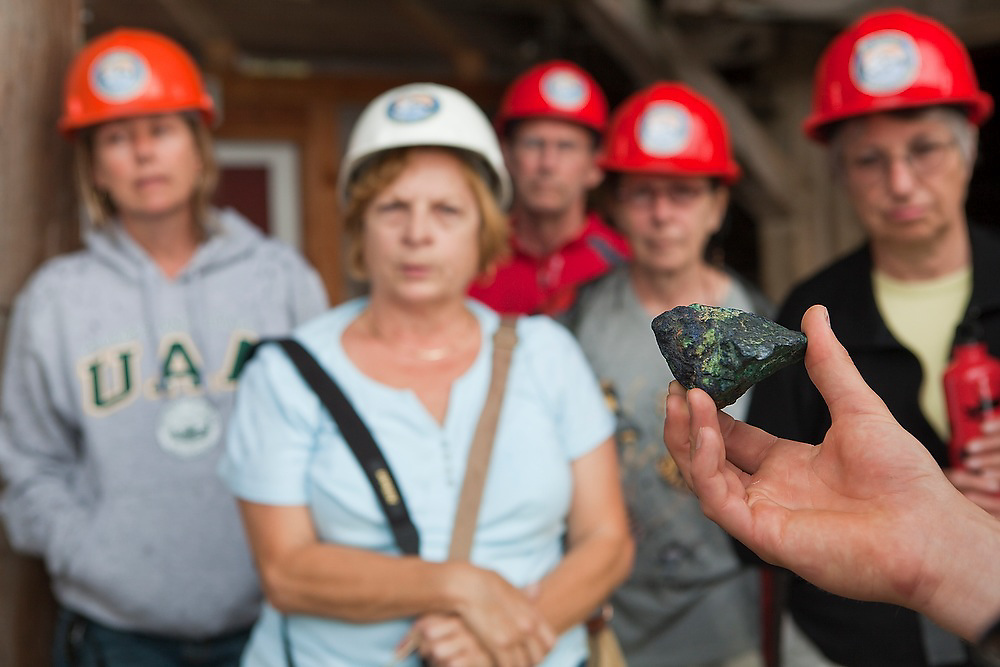 St. Elias Alpine Guides tour guide Ben Wilcox holds out a sample of copper ore during a tour of the impressive mill building in Kennecott, Alaska, site of the historic Kennecott Copper Mine.