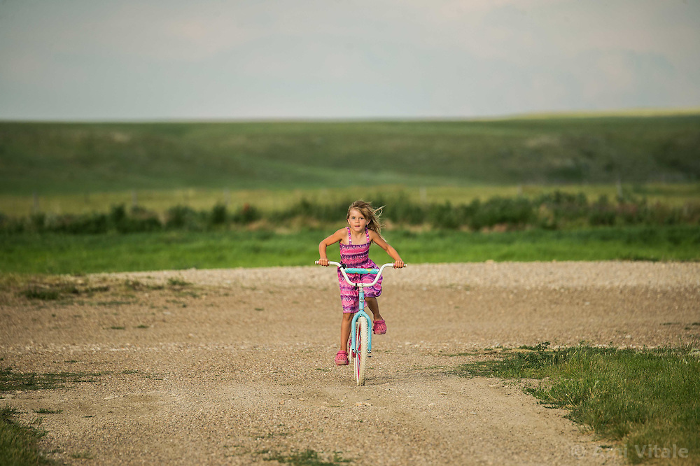 Layla Messerly, the daughter of The Nature Conservancy's Matador Ranch Operations Manager Charlie Messerly rides her bike on the Matador ranch in Eastern Montana. TNC works with 13 ranching families in Eastern Montana  at the Matador ranch &quot;grass bank&quot;. The &ldquo;grass bank&quot; is an innovative way to leverage conservation gains, in which ranchers can graze their cattle at discounted rates on Conservancy land in exchange for improving conservation practices on their own &ldquo;home&rdquo; ranches. In 2002, the <br /> Conservancy began leasing parts of the ranch to neighboring ranchers who were suffering from  severe drought, offering the Matador&rsquo;s grass to neighboring ranches in exchange for their  participation in conservation efforts. The grassbank has helped keep ranchers from plowing up native grassland to farm it; helped remove obstacles to pronghorn antelope migration; improved habitat for the Greater Sage-Grouse and reduced the risk of Sage-Grouse colliding with fences; preserved prairie dog towns and prevented the spread of noxious weeds. (Photo By Ami Vitale)