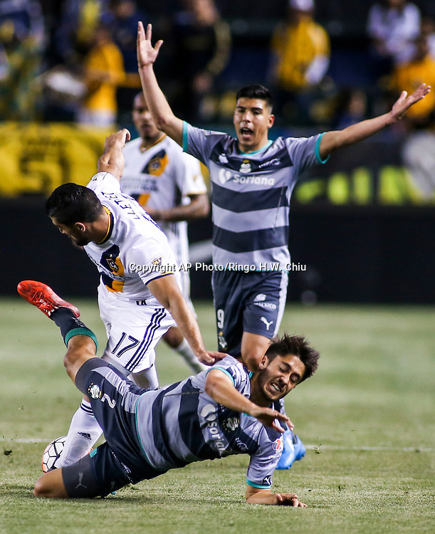 Santos Laguna's forward Luis Angel Mendoza, back, yells as his teammate defender Jose Abella, bottom, crashes with Los Angeles Galaxy's midfielder Sebastian Lletget during the second half of a CONCACAF Champions League quarter final game in Carson, Calif., Wednesday, Feb. 24, 2016. The game ended in a 0-0 draw. (AP Photo/Ringo H.W. Chiu)