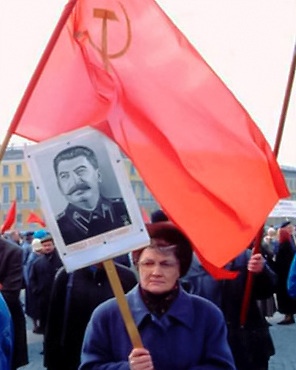 Long after the collapse of the Soviet Union, a middle-aged Russian woman carries a photo of Communist strongman, Soviet leader Joseph Stalin during a parade in St. Petersburg, Russia. Other Communist Party members behind her carry the Hammer and Sickle Soviet flags.