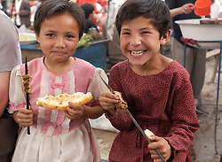 Two young Uyghur girls eating kebabs for lunch at famous Sunday Market in Kashgar on the Silk Road in Xinjiang China
