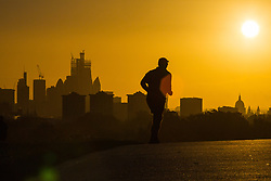 A runner is cast into silhouette as day breaks over London's skyline, seen from Primrose Hill, to the north of the city. London, November 13 2018.