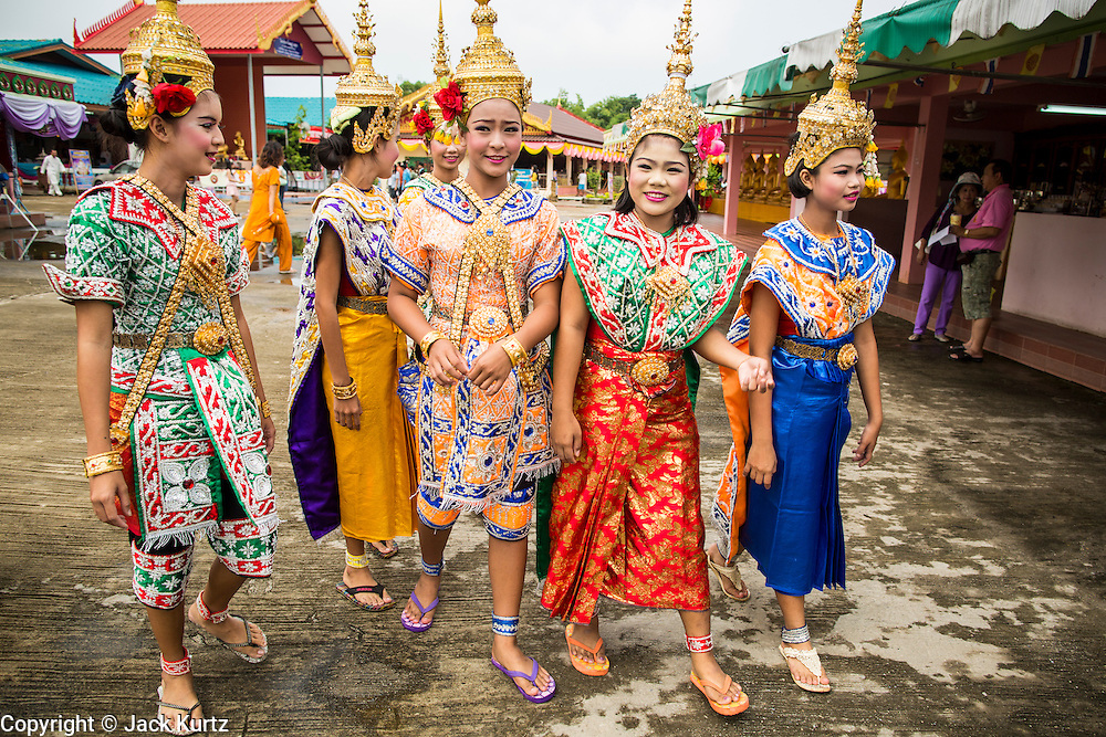 "29 SEPTEMBER 2012 - NAKORN NAYOK, THAILAND:  Thai dancers walk through the temple courtyard during observances of Ganesh Ustav at Wat Utthayan Ganesh, a temple dedicated to Ganesh in Nakorn Nayok, about three hours from Bangkok. Many Thai Buddhists incorporate Hindu elements, including worship of Ganesh into their spiritual life. Ganesha Chaturthi also known as Vinayaka Chaturthi, is the Hindu festival celebrated on the day of the re-birth of Lord Ganesha, the son of Shiva and Parvati. The festival, also known as Ganeshotsav (""festival of Ganesha"") is observed in the Hindu calendar month of Bhaadrapada, starting on the the fourth day of the waxing moon. The festival lasts for 10 days, ending on the fourteenth day of the waxing moon. Outside India, it is celebrated widely in Nepal and by Hindus in the United States, Canada, Mauritius, Singapore, Thailand, Cambodia, Burma , Fiji and Trinidad & Tobago.     PHOTO BY JACK KURTZ"