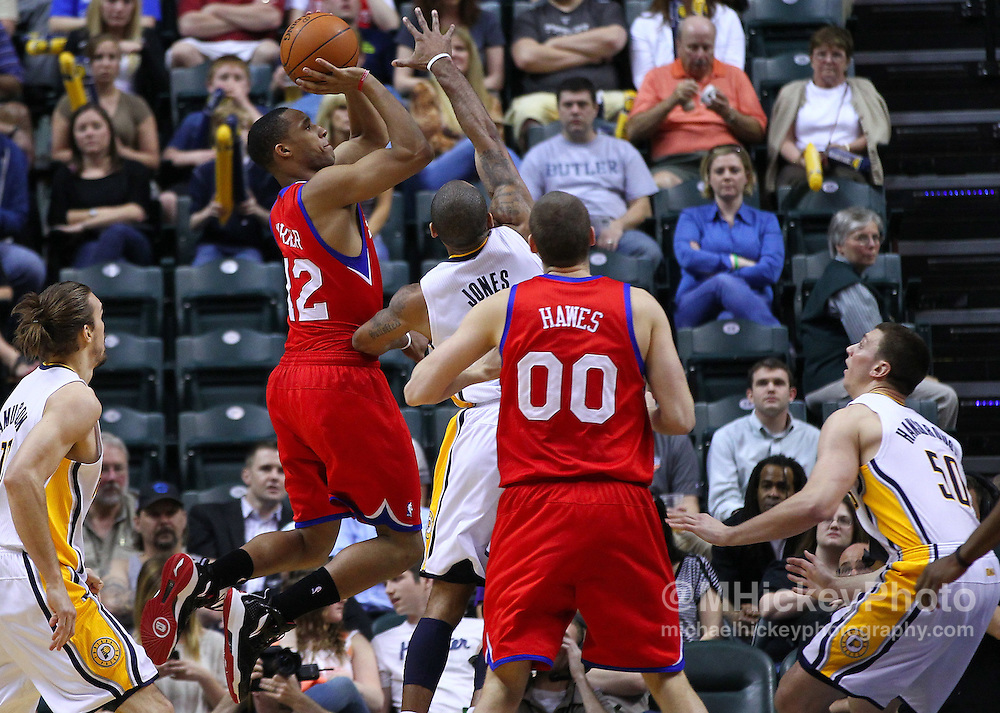 March 14, 2012; Indianapolis, IN, USA; Philadelphia 76ers shooting guard Evan Turner (12) shoots the ball over Indiana Pacers shooting guard Dahntay Jones (1) at Bankers Life Fieldhouse. Indiana defeated Philadelphia 111-94. Mandatory credit: Michael Hickey-US PRESSWIRE