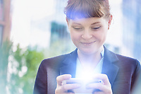 Young attractive businesswoman smiling while using smartphone