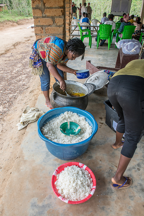 A woman serves rice (Oryza glaberrima) from a large pot in Ganta, Liberia
