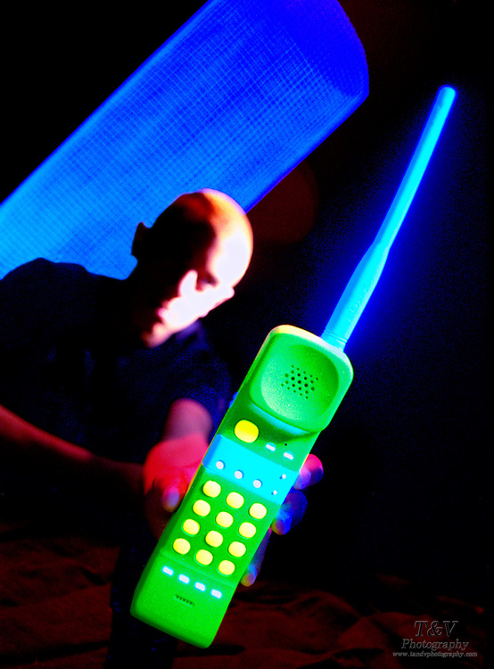 Young man with glowing phone and mesh.Black light