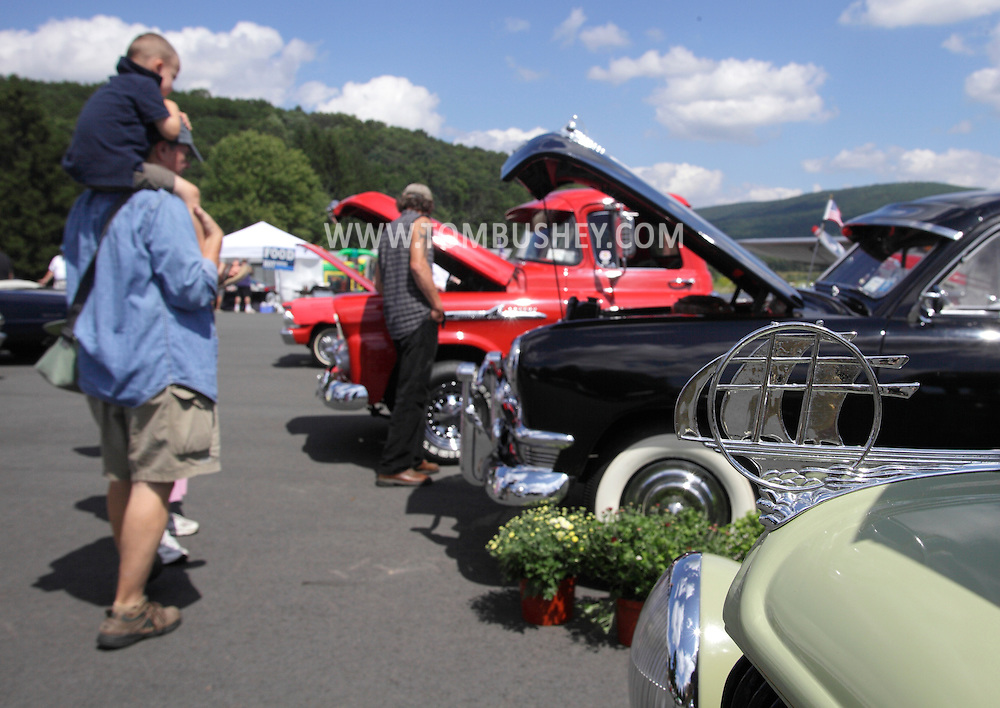 Wurtsboro, NY -  People look at old automobiles on display during a car show at Wurtsboro Airport on Aug. 30, 2009.
