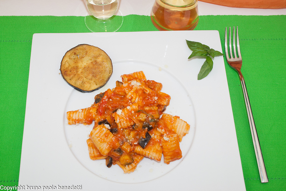 alla norma macaroni with tomato and eggplant sauce side view from above on white dish on green table cloth with eggpkant slice, basil leaves and white wine, italian food of Sicily