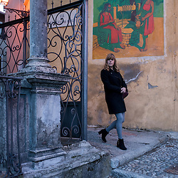 A woman walks under a fresco painting in the ancient town of Santa Maria Del Monte, near Varese, Italy