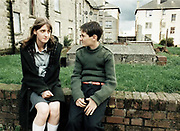 Young girl and young boy sitting on brick wall talking.