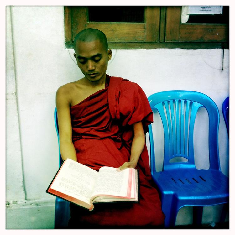 A Monk studies for an upcoming exam. Yangon (Rangoon) Myanmar (Burma) January 2012