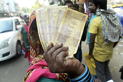 November 13, 2016 - Kolkata, West Bengal, India - A Muslim Women checks her Rs. 500 and Rs. 1000 bank note and long time waiting to exchange it in front of State Bank of India.To facilitate smooth exchange and deposit the old Rs. 500 and Rs. 1000 bank note bank across India remain open for public on Sunday , as announced by Union Government after demonetized Rs.500 and Rs.1000 bank notes to tackle the menace of black money. Indian line up outside the banks to deposit and exchange demonetized bank note from late night. (Credit Image: © Saikat Paul/Pacific Press via ZUMA Wire)