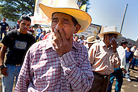 A man covers his nose from the smoke from burning tires as protestor demonstrate in the street Tuesday Sept. 11, 2007, Palin Guatemala. A angry mob took to the streets and went on to burn down the mayors office as well as his home in demonstration after and clash with local police on the previous day. Residents accuse the mayor of, among other things, of bussing voters for the elections on Sept. 9 2007.   (photo by/ Darren Hauck)........