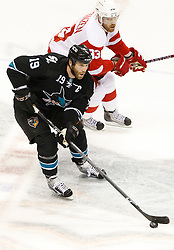 May 8, 2011; San Jose, CA, USA; San Jose Sharks center Joe Thornton (19) controls the puck in front of Detroit Red Wings left wing Johan Franzen (top) during the first period of game five of the western conference semifinals of the 2011 Stanley Cup playoffs at HP Pavilion. Mandatory Credit: Jason O. Watson / US PRESSWIRE